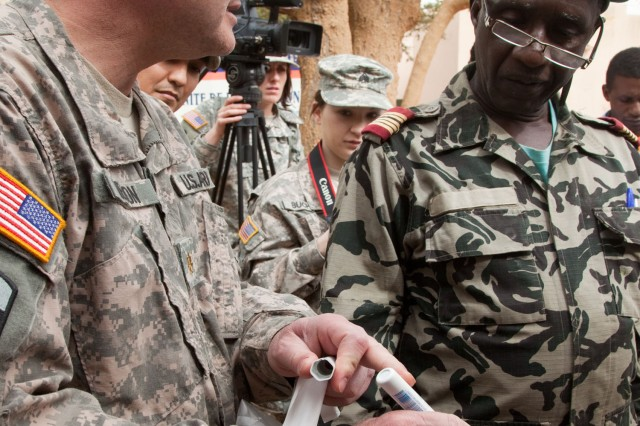 Maj. Dean A. Nelson, 807th Medical Deployment Support Command, Fort Douglas, Utah, explains the use of a battery powered cauterizer pen to Malian Medical Defense Forces Col. Youssouf Traore, in Mopti, Mali, Feb. 7, 2012. The 807th MDSC were in Mali as medical support during Atlas Accord 12.