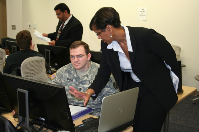 1LT Bryan Upham, Ft. Belvoir WTU, discusses tips on preparing a federal resume with Deshan Mingo, OPM Senior Federal Recruitment Advisor, at a resume writing workshop hosted by the Ft. Belvoir Community Hospital. Photo credit: Erich Langer