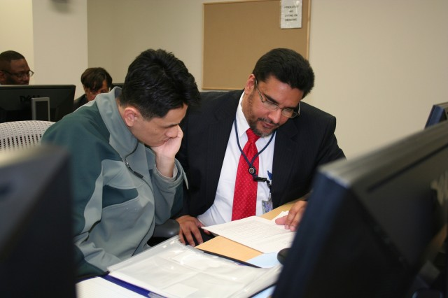 Veteran Jen Welson works with Karlos DelToro, Senior Federal Recruitment Advisor with the Office of Personnel Management as DelToro reviews Welson's federal resume at a Ft. Belvoir, Va. resume writing workshop. Photo credit: Erich Langer