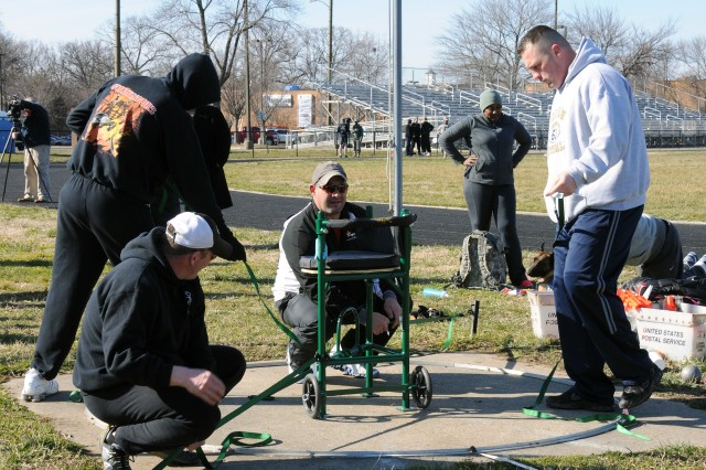 Staff Sgt. Jessie White, coach of the sit shot put, sets up the specially designed chair for the Warrior Games camp at Fort Belvoir, Va., with the help of his team. Only 50 Soldiers will be chosen to compete at the games in Colorado Springs, Colo., April to May 2012.
