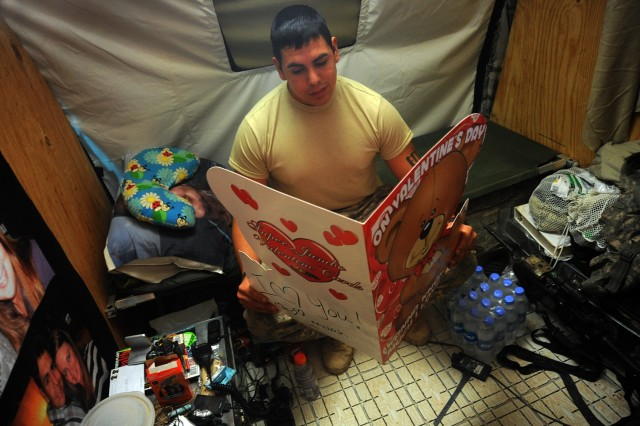 Staff Sgt. Pedro Chavez, 4th Battalion, 23rd Infantry Regiment, reads an over-sized Valentine's card from his wife while on Forward Operating Base Price in Helmand province, Afghanistan.