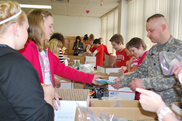 Spc. Frank Beatham helps students of J.F.K. Catholic School in Davenport prepare packages to be sent to Soldiers serving overseas, Feb. 14.