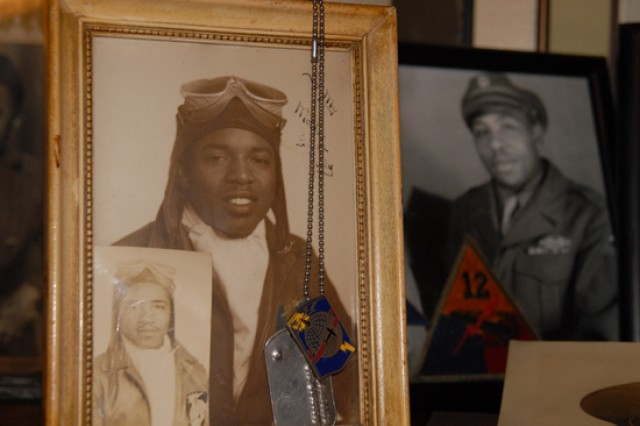 A framed photo of an African-American air crewman from World War II. A family friend gave George Hardy this picture of her father, whom she did not know very well. After some research, Hardy was able to discover the Soldier flew cargo over the Himalayas. The frame is adorned with the Soldier's dog tags. The smaller photo features an unknown Soldier from the same unit.