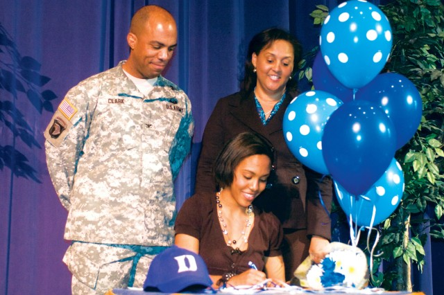 Columbus High School senior Megan Clark signs a letter of intent to Duke as her father, Col. Ron Clark, commander of the 192nd Infantry Brigade, and mother, Simona, watch. Clark, who is considered one of the nation's top pole vaulters, spoke in front of students and faculty about her decision to commit to Duke.