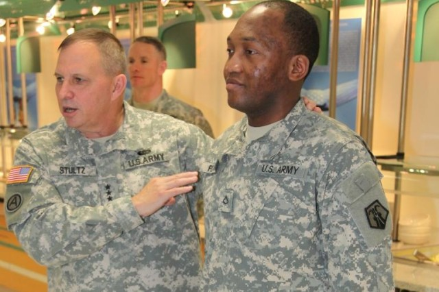 Lt. Gen. Jack C. Stultz, (left) the commanding general of the Army Reserve, talks to members of the 793rd Movement Control Team, 7th Civil Support Command about the role of junior Soldier before he promotes Pfc. Maisonobe G. Fokwakengne, a movement control specialist to the rank of Spc. at the Kleber Dining Facility in Kaiserslautern, Germany Feb 11.