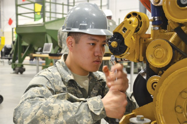 Pvt. Feng Ni works on replacing the water pump on a Stryker during his Stryker Systems Maintainer Course at Fort Lee, Va. In the Stryker bay, there are four stand-alone Stryker engines that students work on as part of their training.