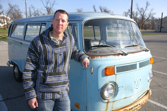 "Spc. Joe Dees stands beside his new love -- ""Betty,"" a 1970 Volkswagen bus. Though he suspects he will be working on her for the rest of his life, Dees will begin its restoration at the Fort Sill, Okla., Automotive Skills Center."
