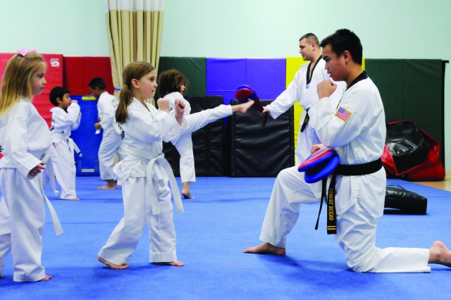 Ava Dennis, 6, left, and Shaylee Maddox, 4, practice their kicks with Samuel Bueno, 13, at a SKIES Unlimited martial arts class Feb. 2. Part of Bueno's black belt training requires him to help teach younger students.
