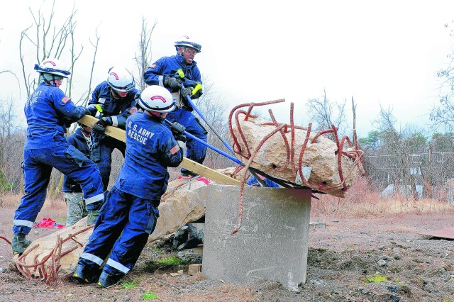 A tactical rescue squad works together to roll a cement slab off an entry point for a burning building.