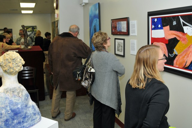 "FORT CARSON, Colo. -- Visitors look at some of the 60 pieces of art housed at Evans Army Community Hospital during the opening of ""Wounded in Action: An Art Exhibition of Orthopaedic Advancements"" Feb. 6. The touring exhibit, which showcases the work of wounded servicemembers, their Families and the orthopedic surgeons who treat these injuries, is open to the public weekdays from 9 a.m. to 4 p.m. through March 2."