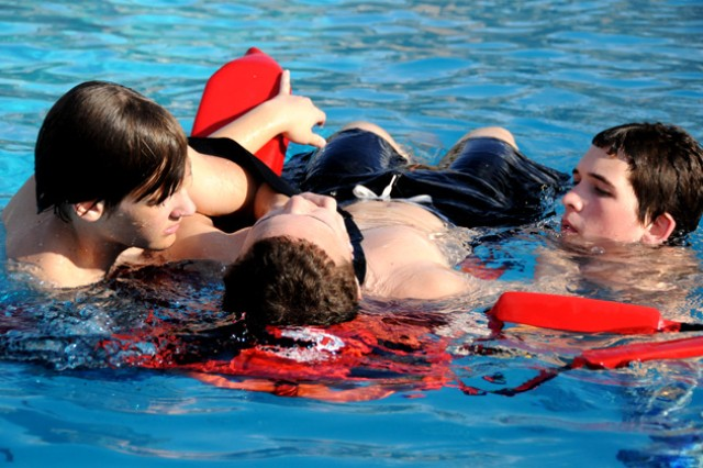 Zach Neudecker and Ryan Murphy, right, perform a deep-water back-boarding rescue exercise using fellow lifeguarding student Ryan Groome as a stand-in victim during a DFMWR lifeguarding course at the Splash! Pool last year.