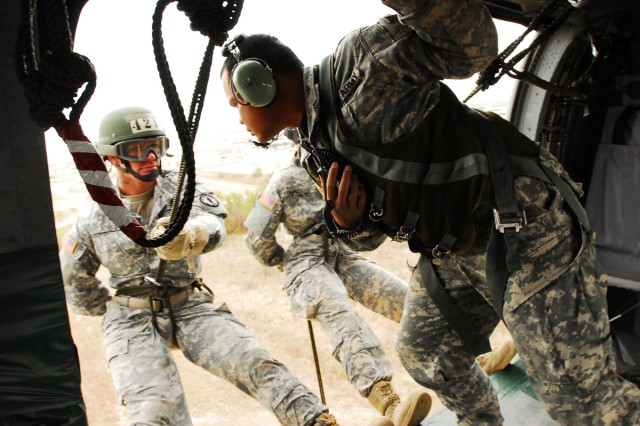 "Sgt. Frank Rosalin, Company B, Warrior Training Center, Fort Benning, Ga., gives a student at Fort Hood's new Air Assault Course the final ""go"" before his 80-foot rappel to the ground at Fort Hood, Texas, Oct. 27, 2011."
