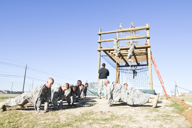"Fort Hood Soldiers do pushups while waiting for their turn at ""The Tough One,"" an obstacle the participants had to complete Oct. 18, 2011, to enter the Air Assault course at Fort Hood, Texas."