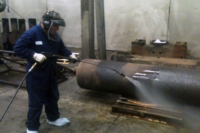 Paul Brown of the Defense Non-Tactical Generator and Rail Equipment Center steam cleans locomotive air tank.