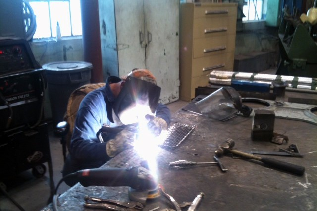 Joel McClellan of the Defense Non-Tactical Generator and Rail Equipment Center performs welding repair on a locomotive spark arrester.