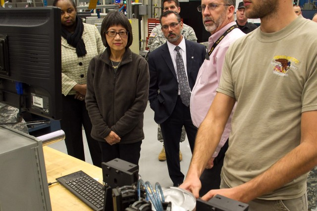 Heidi Shyu, acting assistant secretary of the Army for acquisition, logistics and technology, shown at the center of the photograph, watches as a piston is gauged to ensure it falls within specifications at Anniston Army Depot's Powertrain Flexible Maintenance Facility.