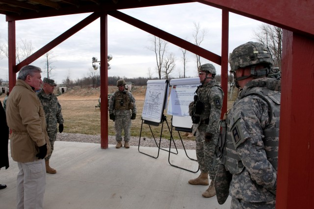 Soldiers with the 157th Infantry Brigade brief David McGinnis, Assistant Secretary of Defense for Reserve Affairs, regarding a base defense live-fire exercise being performed by Soldiers deploying to the Horn of Africa as part of a multinational observation force during a tour of Camp Atterbury Joint Maneuver training Center, Ind., Feb 13. McGinnis was in Indiana at the invitation of the Indiana National Guard and First Army to tour facilities programs for mobilization and post-deployment care of Soldiers.