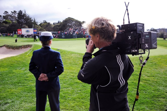 PEBBLE BEACH, Calif. - A cameraman gets a close-up shot of U.S. Coast Guard Seaman Jordan Vaughn as she waits to take possession of the 15th hole pin during play at the AT&T Pebble Beach National Pro-Am.
