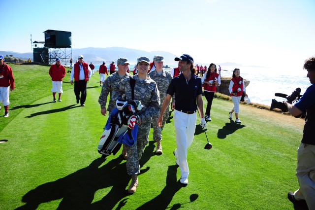 PEBBLE BEACH, Calif. - Pfc. Courtney Neuman, 229th Military Intelligence Battalion, acts as caddy for singer Kenny G during the final hole of the 3M Celebrity Challenge at Pebble Beach Feb. 8. The popular charity event is part of the AT&T Pebble Beach Pro-Am tournament and coincides with Military Appreciation Day in which active-duty military, law enforcement and firefighters are admitted to the tournament for free. Kenny G has chosen service members from the crowd annually to act as his caddy and walk the course with celebrity players.