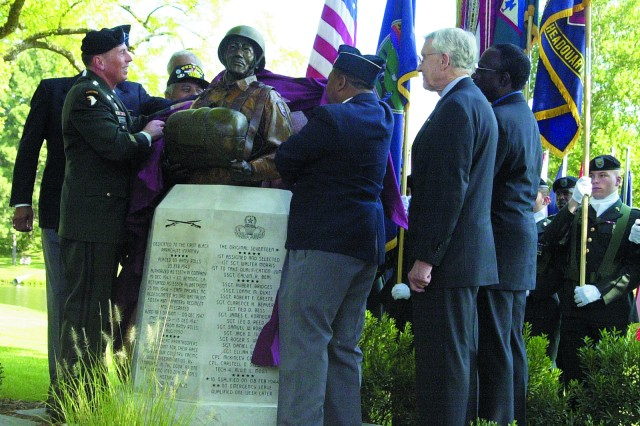 "Then-Combined Arms Center and Fort Leavenworth Commander Lt. Gen. David Petraeus and 555th Parachute Infantry ""Triple Nickles"" Association President Joseph Murchison unveil a bust honoring members of the first and only all-black World War II parachute battalion with retired 1st Sgt. Walter Morris, one of the original members of the 555th; retired Lt. Gen. Robert Arter, Civilian Aide to the Secretary of the Army for the state of Kansas; and the bust's sculptor Eddie Dixon at a dedication ceremony Sept. 7, 2006. The bust is located at Smith Lake near the Buffalo Soldier Monument, which was also created by Dixon. The bust is modeled after Morris, who was also the first black enlisted man accepted for airborne duty."