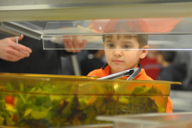 Aaron Ruiz, a 5-year-old Marshall Elementary student, glances at Friday's selection at the salad bar. Barbara McConnell, the school's new cafeteria manager, offers different fruits and vegetables each day along with the main entree to encourage healthy eating and keep in compliance with federal nutrition guidelines. (Photo by Megan Locke Simpson, staff, The Fort Campbell Courier.)