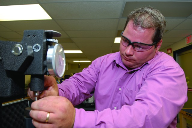 Dan Hodle of Tobyhanna Army Depot uses a Rockwell Hardness tester, which is a a hardness scale based on the indentation hardness of a material. The Rockwell test determines the hardness by measuring the depth of penetration of an indenter under a large load compared to the penetration made by a lighter preload.