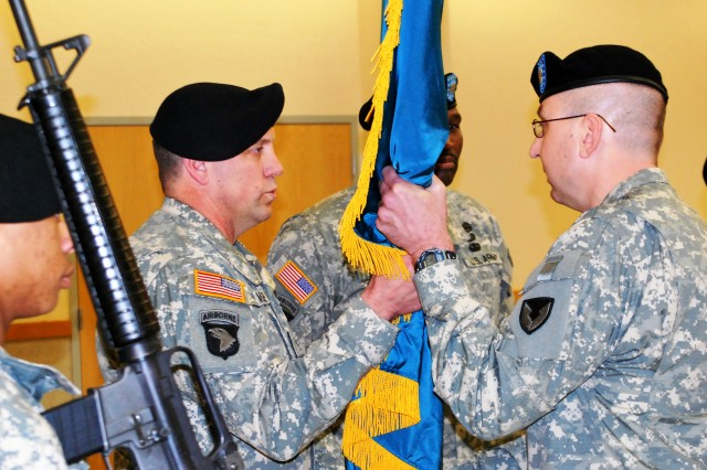 Newly promoted Lt. Col. Andrew DeKever passes the unit colors to Command Sgt. Maj. Rodger Mansker,  404th Army Field Support Brigade during an Army Field Support-Battalion-Alaska (Provisional) change of authority ceremony Feb. 10 at Joint Base Elmendorf-Richardson, Alaska. The morning also saw outgoing commander, Lt. Col. Nathaniel Rivers, retire after nearly 31 years of Army service. (Photo by Jon Connor, ASC Public Affairs)