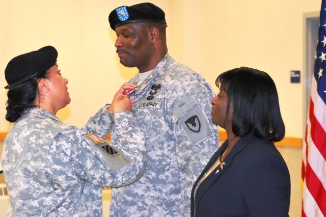 Col.  Leafaina Yahn, commander, 404th Army Field Support Brigade, awards Lt.  Col. Nathaniel Rivers the Legion of Merit during his retirement ceremony Feb. 10 at Joint Base Elmendorf-Richardson, Alaska. Rivers' wife, Ramona, proudly looks on. (Photo by Jon Connor, ASC Public Affairs)