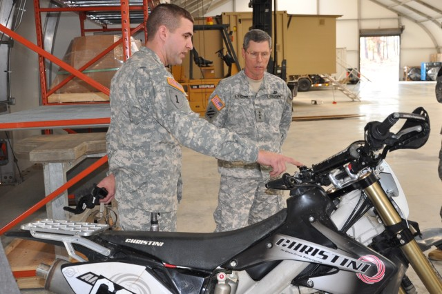 FORT A.P. HILL, Va. -- Lt. Gen. John Sterling, deputy commanding general for U.S. Army Training and Doctrine Command, receives an overview on the specs of a Christini 450 off-road motorcycle by Sgt. 1st Class Stuart Tempalski, a mechanic for the U.S. Army Asymmetric Warfare Group, during Sterling's visit Feb. 15, at an AWG training facility at Fort A.P. Hill, Va. Through firsthand observation, the AWG identifies and develops solutions for enemy tactics, techniques and procedures that attempt to exploit friendly capability gaps, to include those that may exist in mobility operations. Tactical mobility is one of many areas that is continuously assessed and analyzed by AWG to fill capability gaps. The AWG provides operational advisory support globally to Army and Joint Force commanders to enhance Soldier survivability, combat effectiveness and enable the defeat of current and emerging threats in support of Unified Land Operations. (U.S. Army photo by Maj. Sonise Lumbaca)