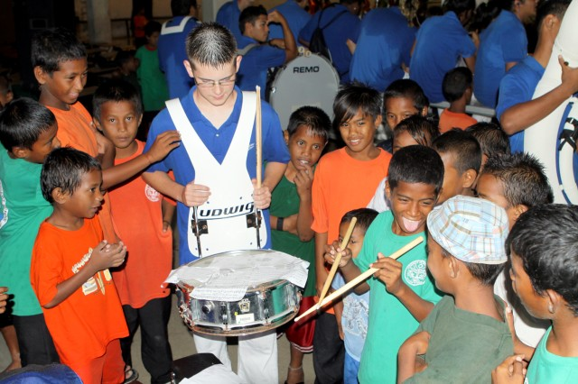 Kwajalein Jr./Sr. High School Band member Stephen Parrish Jr. lets Ebeye children try out his drums while waiting for the ceremony to start Feb. 9.