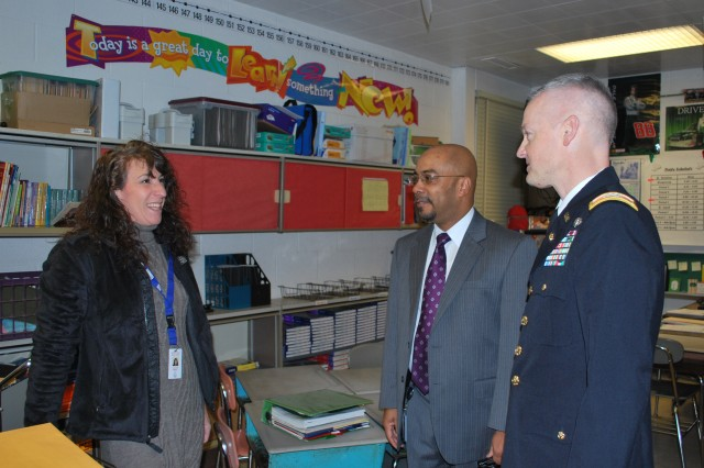 Col. William 'Bill' Montgomery, chief of staff for the U.S. Army Communications-Electronics Command, expresses his appreciation to sixth grade Havre de Grace Middle School teacher, Kathy Bradley, for her service as a military spouse. Bradley's husband, Staff Sgt. Christopher Bradley serves with the Maryland National Guard. Montgomery presented remarks Feb. 14 during the school's honors breakfast recognizing students who achieved a 3.5 grade point average or better in the last report card rating cycle.