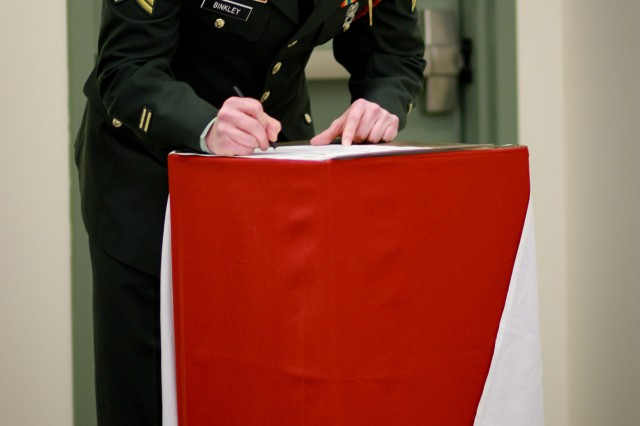 FORT DRUM, N.Y. - Army Sgt. Christopher Binkley, C Troop, 1st Squadron, 89th Cavalry Regiment signs his name to a charter during a non-commissioned officer induction ceremony Feb. 17. (Photo by Capt. Michael Greenberger)