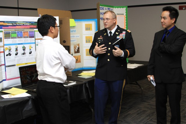 Col. Jeff Hall, commander of the U.S. Army Corps of Engineers Savannah District, and Jimmy Luo, an electrical engineer at the Corps' Fort Stewart field office, speak with a student about his science project at the 2012 Georgia Tech Regional Science and Engineering Fair, Feb. 16, 2012.