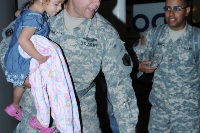 Maj. Federico Martinez, 246th Mortuary Affairs Company Commander, moves his baggage, while holding her daughter, Lizbeth (4), during the departure of the unit to a CONUS Mobilizations Station.