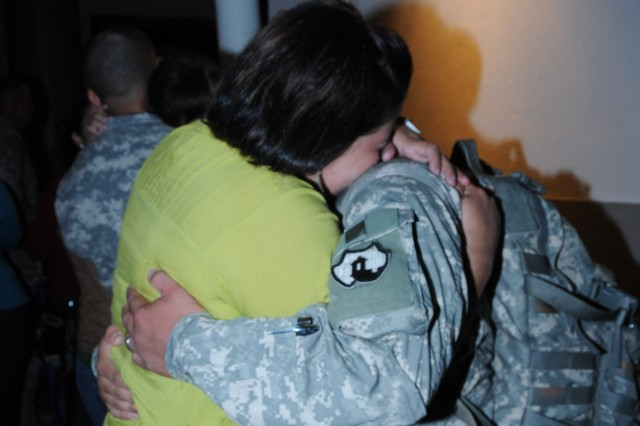 Recently married Yaritza Rivera (left) and Staff Sgt. Christopher Marty (right) hug, moments before boarding the plane that would take him to a mobilization station at the Continental United States, as part of 246th QM Co. preparation for deployment to Afghanistan. Rivera and Marty married the day before of the unit's mobilization.
