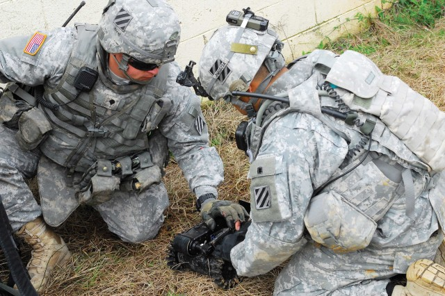 Two Soldiers prepare a robot for a mission Wednesday as part of the experiment. Soldiers at Fort Benning, Ga., tested four small robots last week to get a better idea how they might help Soldiers in recon missions and the detection of improvised explosive devices.
