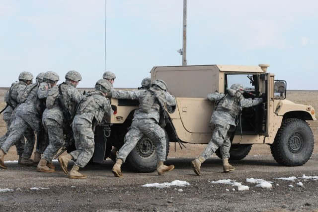"FORT RILEY, Kan. - Soldiers of the 1st Engineer Battalion, 1st Heavy Brigade Combat Team, 1st Infantry Division, push a HUMVEE as part of the Stress Shoot station during the Diehard Stakes held on Fort Riley, Feb. 10, 2012 "" Feb. 21, 2012. As a result of this competition, Sappers of the Diehard Battalion were tested; physically and mentally, which enabled their leaders to evaluate the Soldiers level of training."