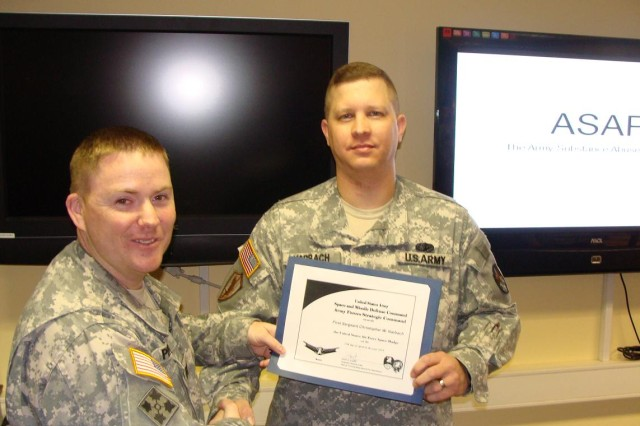 1st Sgt. Christopher Harbach is presented a certificate signifying he has received the Army space badge. Harbach joined the Army 20 years ago this August.