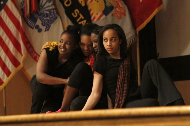 "West Point Class of 2015 Cadet Zena Williams, Class of 2012 Cadet Ashley Anthony, Class of 2012 Cadet Shalela Dowdy and Class of 2015 Cadet Sarah Locke huddle on stage at the conclusion of an interpretive dance to Nina Simone's ""Four Women."" The 2012 Black History Month Observance at West Point featured powerhouse performances by cadets at Robinson Auditorium on Feb. 15."