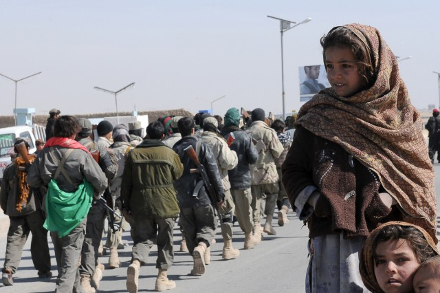Children in the village of Howz-E-Madad watch the Afghan Liberation Day parade pass through the local bazaar Feb. 15.