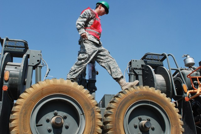 Pfc. Andrew Coffman, 227th Quartermaster Company, inspects a load of heavy equipment that had been turned in at Camp Liberty, Iraq. The 402nd Army Field Support Brigade operated seven turn-in facilities in Iraq assisting units heading home during the closing months of Operation New Dawn.