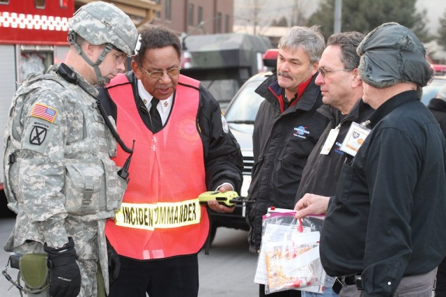 """At Camp Red Cloud Feb. 16, U.S. Army Garrison Red Cloud fire chief John Cook (second from left) confers with other emergency response officials on the next steps in handling a biological attack during antiterrorism exercise ADAPTIVE FOCUS, At left is Lt. Col. Christopher Durham, 2nd Infantry Division. """" U.S. Army Photo by Kevin Jackson"""