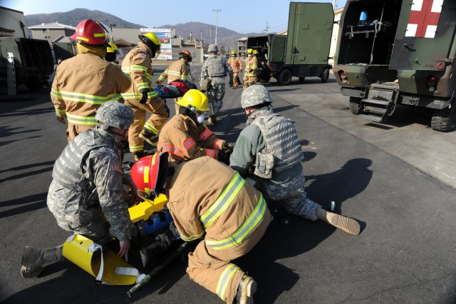 """During a mock car bombing outside the Camp Red Cloud commissary Feb. 16, smoke issues from a vehicle in which explosives were set off as Soldiers fall to the ground and pretend to be injured by the blast. The training episode was one of numerous terror incidents staged during antiterrorism exercise ADAPTIVE FOCUS, held Feb. 15-16 at Area I installations. Along with the 2nd Infantry Division and U.S. Army Garrison Red Cloud, South Korean troops and civil authorities took part. """" U.S. Army Photo by Franklin Fisher"""