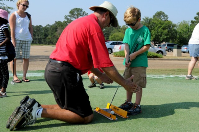 Ronnie Mobley, Silver Wings Golf Course golf pro, works with Alerik Nedostup on the practice putting greens during the first EFMP golf clinic last year. EFMP is a program designed to help Families with special needs get the support they need.