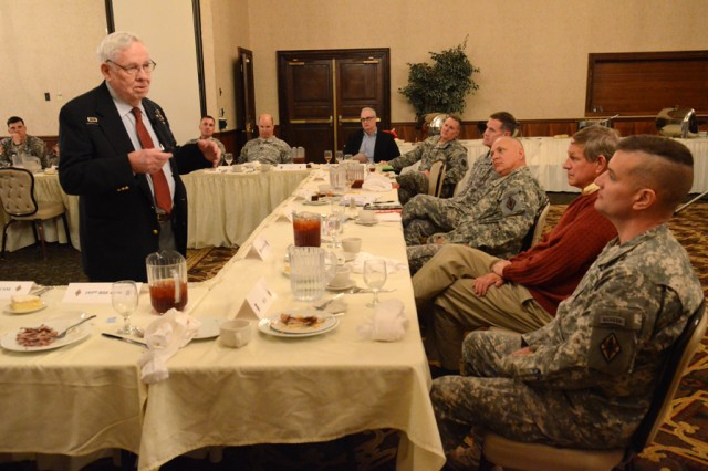 T. Moffatt Burriss, standing, responds to a question from Col. Craig Currey, deputy commanding officer of Fort Jackson, seated at right. Burriss, a 92-year-old World War II veteran, was the guest speaker for the quarterly Profession of Arms luncheon Feb. 14.