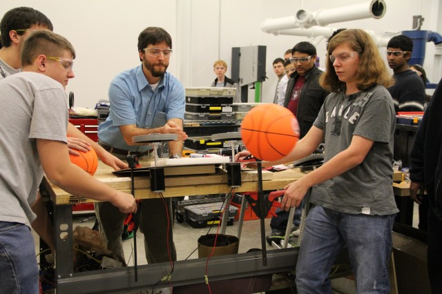 (Left to right) Spenser Puffenbarger, team advisor Marc Evans and Christopher Flake test the robot's firing apparatus.