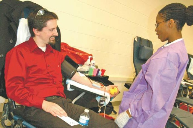 Phlebotomist Quinishia Reed draws blood from CECOM employee Jeff Shields during the 9th AML blood drive Feb. 3.