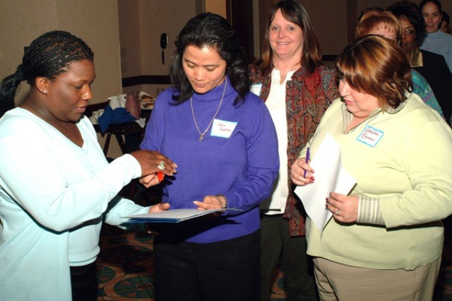 Shoshana Johnson (left), the first African-American woman prisoner of war (she survived 22 days as POW in Iraq), signs autographs after speaking at the Iowa/Illinois Chapter of Women in Defense Symposium, held at the Isle of Capri in Bettendorf, Iowa, March 8, 2005.