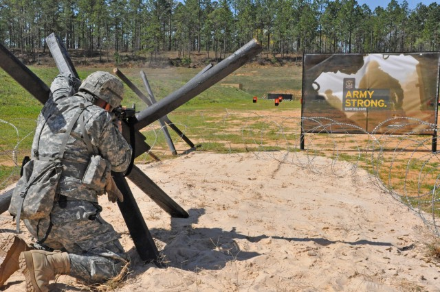 """FORT BENNING, Ga. -- A Soldier dodges obstacles while shooting his rifle on one of four combined arms courses at Krilling Range during the 2011 U.S. Army Small Arms Championships. More than 320 Soldiers from across the Army are registered to compete in the 2012 """"All-Army,"""" which will be the highest total in 19 years. (Photo by Michael Molinaro, USAMU PAO)"""