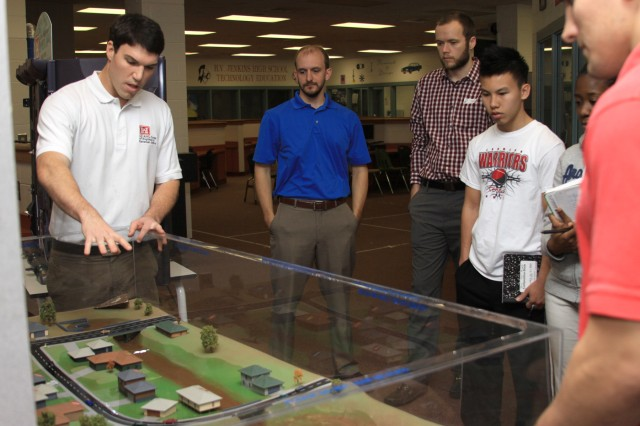 Jason Lavecchia (left) a civil engineer with the U.S. Army Corps of Engineers Savannah District explains flood damage prevention techniques with an interactive flood plain model.